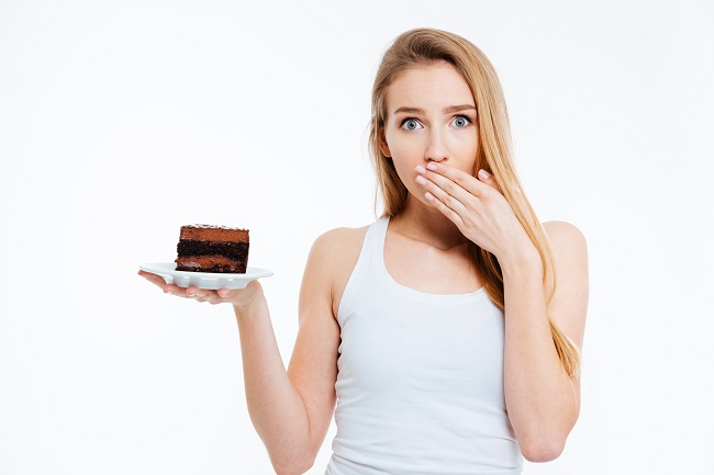 beautiful-confused-young-woman-on-diet-holding-piece-of-chocolate-cake-over-white-background_SY-n8zCBs چگونه میتوان 2 هفته ای 20 كیلو لاغر كرد ؟ _ حتما بخوانید