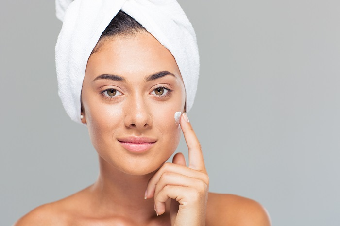 attractive-young-woman-with-towel-on-head-applying-cream-on-face-over-gray-background-looking-at-camera_700 ماسک های گیاهی و طبیعی خانگی برای پوستی درخشان